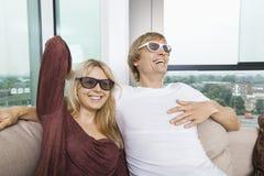 Pares felices que llevan los vidrios 3D mientras que se sienta en el sofá en casa Imágenes de archivo libres de regalías