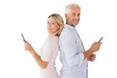 Pares felices que mandan un SMS en sus smartphones Imágenes de archivo libres de regalías
