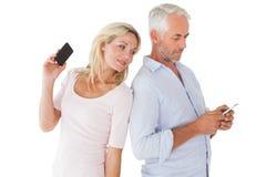 Pares felices que mandan un SMS en sus smartphones Foto de archivo libre de regalías