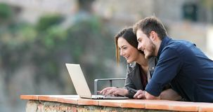 Pares felices que mecanografían en un ordenador portátil que busca el contenido
