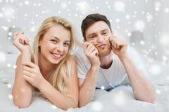 Pares felices que mienten en cama en casa Foto de archivo libre de regalías