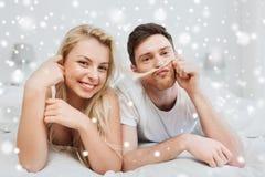 Pares felices que mienten en cama en casa Imagen de archivo libre de regalías