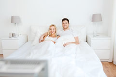 Pares felices que mienten en cama en casa y la TV de observación Foto de archivo