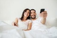 Pares felices que mienten en cama en casa y la TV de observación Fotografía de archivo libre de regalías
