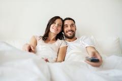 Pares felices que mienten en cama en casa y la TV de observación Fotos de archivo