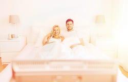 Pares felices que mienten en cama en casa y la TV de observación Imagen de archivo