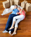 Pares felices que mienten en el suelo en su nueva casa Imagen de archivo