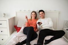 Pares felices que mienten en la cama que ve la TV imágenes de archivo libres de regalías