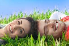 Pares felices que mienten en la hierba Fotografía de archivo