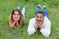 Pares felices que mienten en la hierba en el campo Foto de archivo libre de regalías