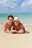 Pares felices que mienten en la playa arenosa Imagenes de archivo