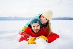 Pares felices que mienten en nieve Imagenes de archivo