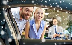 Pares felices que miran el coche interior en salón del automóvil Fotos de archivo libres de regalías