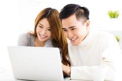 Pares felices que miran el ordenador portátil en sala de estar Fotografía de archivo libre de regalías