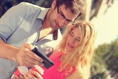 Pares felices que miran el teléfono móvil Fotografía de archivo libre de regalías