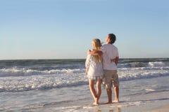 Pares felices que miran hacia fuera sobre el océano mientras que camina en la playa Imagenes de archivo