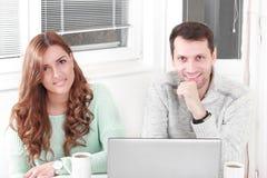 Pares felices que miran la cámara con el ordenador portátil en casa fotografía de archivo libre de regalías