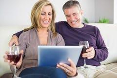 Pares felices que miran su PC de la tableta y que beben el vino imagenes de archivo
