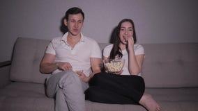 Pares felices que miran una película en la TV que se sienta en un sofá en casa almacen de video