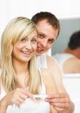 Pares felices que miran una prueba de embarazo Foto de archivo libre de regalías