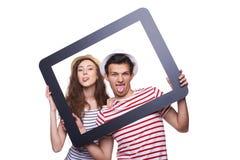 Pares felices que muestran la lengua a través de marco de la tableta Imagen de archivo libre de regalías