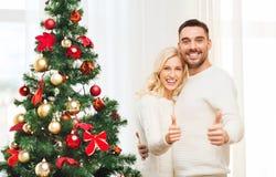 Pares felices que muestran los pulgares para arriba con el árbol de navidad Imagen de archivo