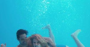 Pares felices que nadan bajo el agua almacen de video