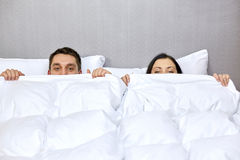 Pares felices que ocultan debajo de la manta en cama Foto de archivo libre de regalías