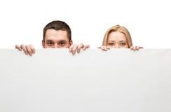 Pares felices que ocultan detrás de tablero en blanco blanco grande Imágenes de archivo libres de regalías