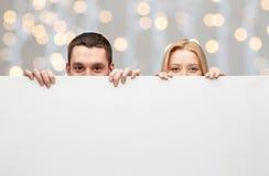 Pares felices que ocultan detrás de tablero en blanco blanco grande Imagen de archivo libre de regalías