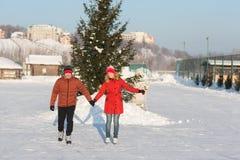 Pares felices que patinan en el invierno de la pista Fotos de archivo