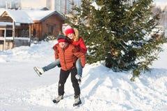 Pares felices que patinan en el invierno de la pista Foto de archivo