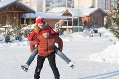 Pares felices que patinan en el invierno de la pista Foto de archivo libre de regalías