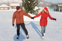 Pares felices que patinan en el invierno de la pista Fotografía de archivo