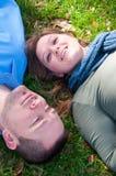 Pares felices que ponen en la hierba Fotografía de archivo libre de regalías