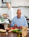 Pares felices que preparan la comida vegetariana y que hacen el quehacer doméstico Fotos de archivo libres de regalías