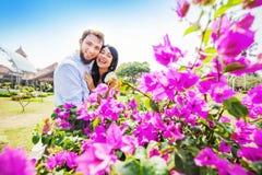 Pares felices que presentan cerca de arbusto con las flores rosadas fotos de archivo libres de regalías