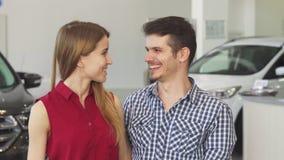 Pares felices que presentan con llaves del coche a su nuevo auto almacen de metraje de vídeo