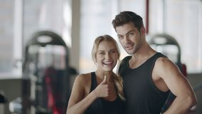 Pares felices que presentan en gimnasio moderno La mujer sonriente que muestra los pulgares sube gesto almacen de video