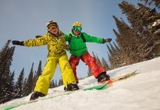 Pares felices que presentan para los snowboarders Imágenes de archivo libres de regalías