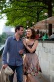 Pares felices que recorren en una calle y un abrazo Fotos de archivo libres de regalías