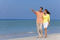 Pares felices que recorren y que señalan en una playa Foto de archivo