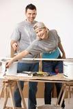 Pares felices que renuevan el nuevo hogar de pintura Imagenes de archivo