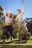 Pares felices que saltan en el parque Fotos de archivo