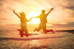 Pares felices que saltan en la playa Fotos de archivo libres de regalías