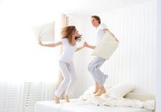 Pares felices que saltan y que se divierten en cama Imagen de archivo