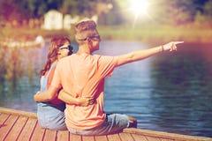 Pares felices que señalan el finger en litera del río del verano Foto de archivo libre de regalías