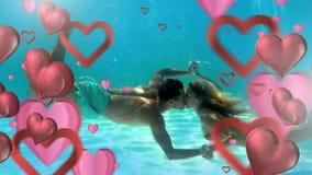 Pares felices que se besan bajo el agua con los corazones para el día de San Valentín almacen de metraje de vídeo