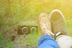 Pares felices que se besan de los jóvenes en el amor que se sienta en la tierra y la música que escucha en parque verde del samme Fotos de archivo