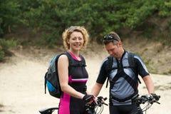 Pares felices que se colocan al aire libre con las bicis Foto de archivo libre de regalías